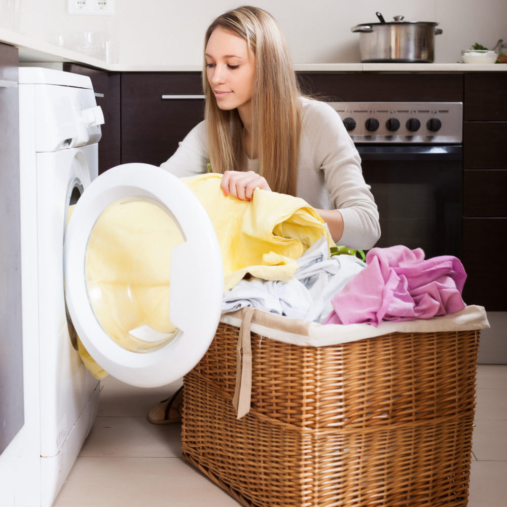 Home laundry. Blonde woman loading clothes into washing machine in home
